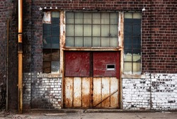 Old Rusted Metal Doors on Abandoned Decaying Brick Factory Building in Urban City, Factory, Working Class District