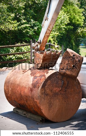 Old rusted metal underground heating oil storage tank. Tank was removed using excavation equipment as a precaution against environmental pollution due to oil leakage. - stock photo