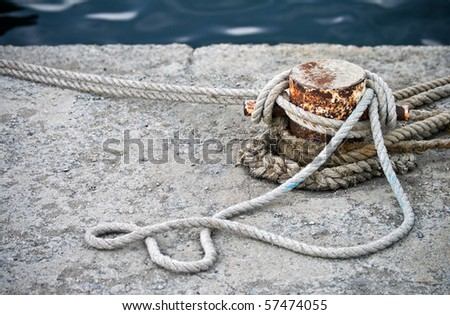 Old rusted mooring bollard with knotted nautical ropes