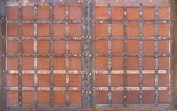Old rusted opaque metal gate with a square pattern of fittings