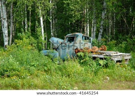 Old rusted pickup truck sitting in a field