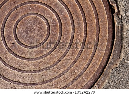 Old rusted round sewer manhole closeup abstract fragment