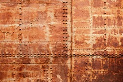 Old rusted ship hull fragment, iron sheets with rivets, background photo texture