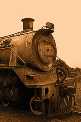 OLD RUSTED STEAM LOCOMOTIVE AT AN ABANDONED STATION IN SEPIA