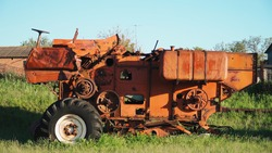 Old rusted tractor aged on farm land. Abandoned agricultural machinery
