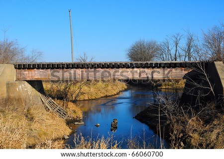 Old rusted train bridge with blue sky and creek