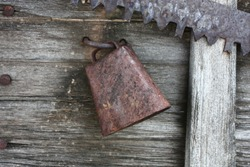 Old rusted  vintage cow bell hanging on a wooden sideboard .