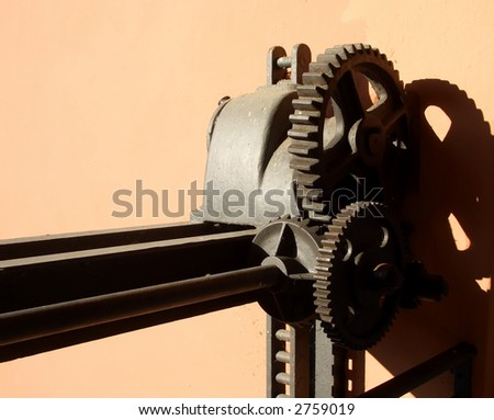 Old rusted watergate gears against brown wall casting strong shadows