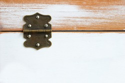 Old rustic hinge on box with white scratched paint / Hinge on grunge texture background