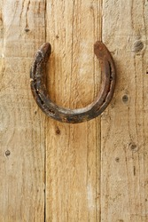 Old rustic horseshoe hanging on door said to bring good fortune and luck according to superstition