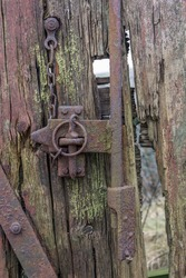 Old rustic metal hinge and lock on old wooden shed. Mold and rust in the background.