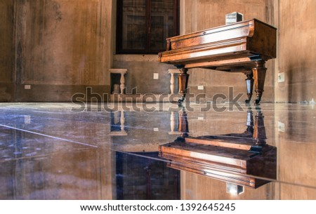 Old rustic piano on stands with wheels in empty room with polished glass look floor making reflection of piano and whole room symmetrical #1392645245