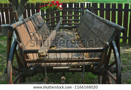 Old rustic vintage carriage in front of fence in backyard