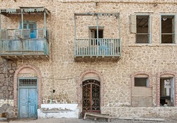 Old rustic wooden doors and balcony on wall of abandoned traditional egyptian house