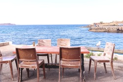 Old rustic wooden table restaurant with sea view blue water white sky no body coastal photography