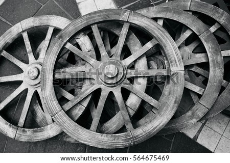 Old rustic wooden wagon wheels. Black and white