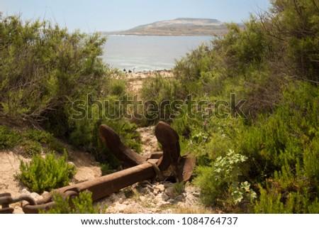 Old rusty abandoned anchor on the coastline of Maltas beach