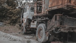 Old, rusty, abandoned truck crane in the woods. Old, rusty interior elements, controls and indicators. Interior close-up.