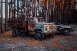 Old rusty abandoned truck in the forest.