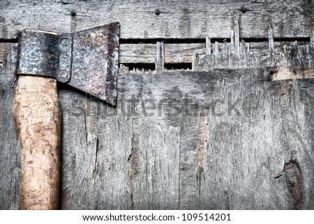 Old rusty axe on the textured wooded background