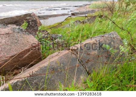 Old rusty barbed wire at the site of an  concentration camp on the shore of the White Sea in stormy weather