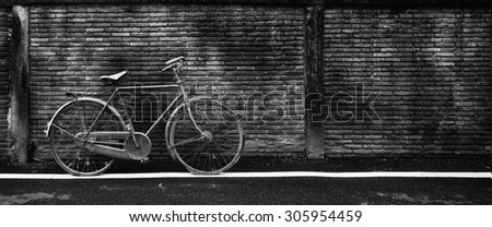Old rusty bicycle against an old wet brick wall, black and white