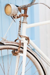 Old rusty bicycle leaning against blue door. Formentera island. Spain. Shallow deep of focus.