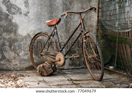 old rusty bicycle over a grunge background - stock photo