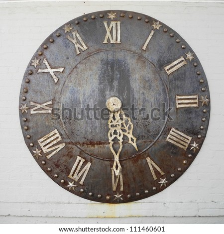 Old rusty big street clock on wall of the building