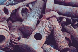 Old rusty bolts and nuts. Fasteners on the trash can. The iron bolts are rusty. Corrosion of metal on the screws.