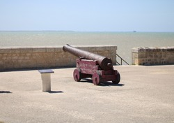 Old rusty cannon by the sea