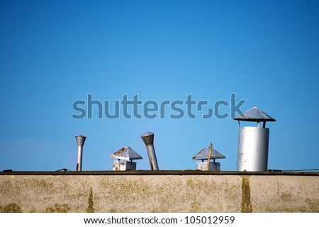 Old rusty chimneys on building rooftop