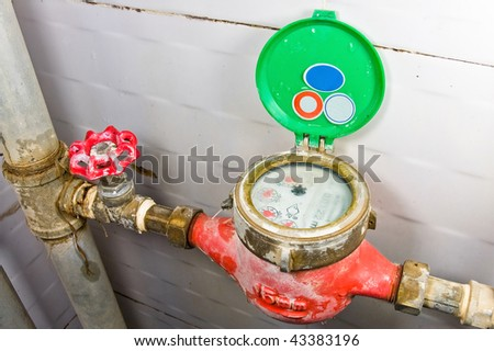 Old rusty colorful red brass valve and red and green water-meter with rusty  tubes on white background.