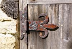 Old rusty door hinge on wooden door