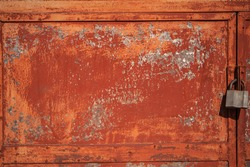 old rusty door with a padlock, fragment of a terracotta iron door with a lock, cracked paint on metal