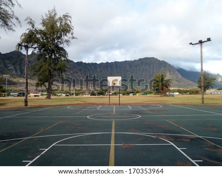 Old rusty Empty Outdoor Basketball Court with lights on wooden poles and pine needles on the court during the day with Mountain range in the background in Waimanalo Beach Park on Oahu, Hawii.