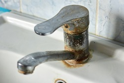 Old, rusty faucet in the kitchen, limestone, scum, need a replacement.