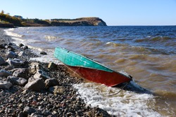 old rusty fishing boat lies on the pebble coast of the river. The waves of the tide roll over the little iron man and break into spray and foam on the side, bow and stern of the boat.