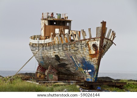 Old rusty fishing trawler being broken up on the shore, bow to camera