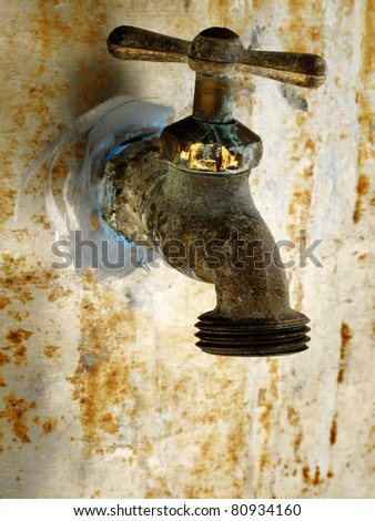 Old rusty garden faucet on wall of home or shed