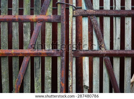 Old rusty gate from wooden plank tied up by a steel cable