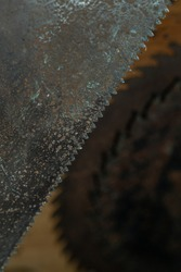 Old rusty hand saw with a disk saw on background. High quality photo