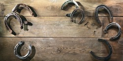 Old rusty horse shoes lying on a wooden barn floor