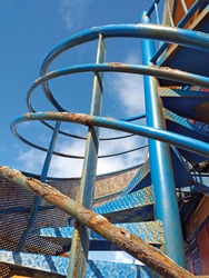 Old rusty iron blue spiral staircase against a blue sky. Architecture detail. Blue exterior staircase with vintage retro style rusty railing in the French West Indies.
