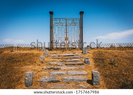 Photo of  Old rusty iron gate in the middle of a field leading to nowhere. Concept of purgatory, limits, frontiers and freedom