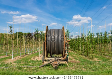 Old rusty irrigation hose reel, Agricultural Travelling Irrigator or Hose Reel Irrigation Sprinkler Machine set up on agricutural land for serving irrigation system of farm in countryside of Germany. #1433473769
