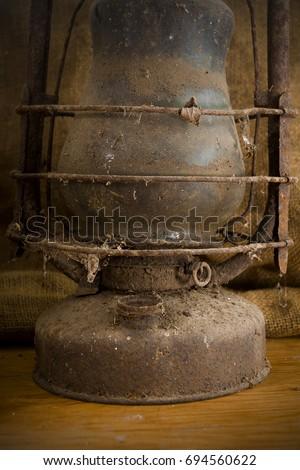 Old rusty kerosene lamp on the kitchen table