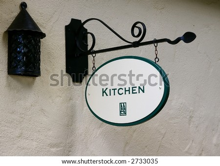 """Old rusty lantern and """"Kitchen"""" sign on stucco wall"""