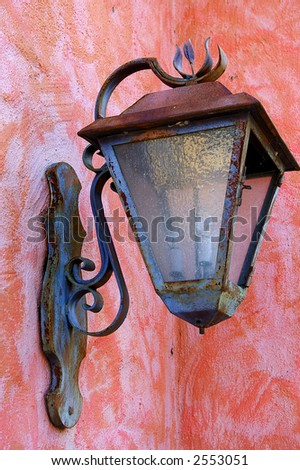 Old rusty lantern on the colorful stucco wall