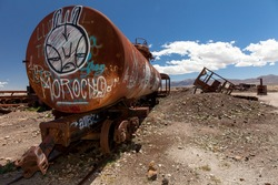 Old rusty locomotive with graffiti in the front .Uyuni, train cemetery, Bolivia. Blue sky background